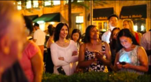 Figure 12. I am out of focus at left, scanning the crowd on the street. The girl on the left may have guessed what I was doing, or is amused by the photographer. Wanda is enjoying the music but also may be aware I am looking. Wanda's friend is preoccupied with her smart phone.